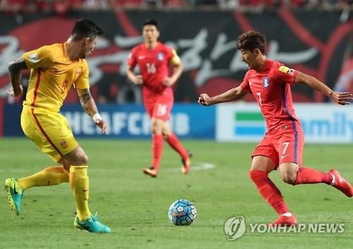 South Korean midfielder Son Heung-min (R) tries to dribble past Feng Xiaoting of China during their Asian World Cup qualifier at Seoul World Cup Stadium on Sept. 1, 2016. (Yonhap)