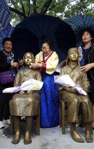 "Lee Yong-soo (C), a former ""comfort woman,"" wipes the face of a statue representing the victims, which was unveiled at Shanghai Normal University on Oct. 22, 2016. (Yonhap)"
