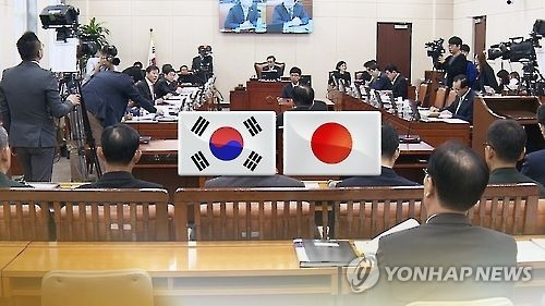 This undated captured image from Yonhap News TV shows the national flags of South Korea and Japan against background of a parlimentary hearing in Seoul. (Yonhap)