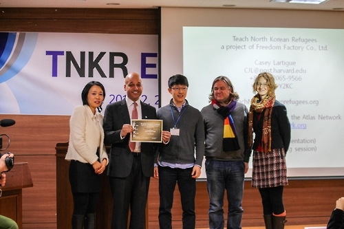 Lee Eun-koo (L) and Casey Lartigue (2nd from L), co-founders of the Teach North Korean Refugees (TNKR) Global Education Center, pose for a photo with the winner of the first English speech contest hosted by the center on Feb. 28, 2015, in this photo provided by TNKR. (Yonhap)