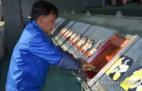 This undated file photo shows a North Korean man working at a bag factory in Pyongyang. (Yonhap)