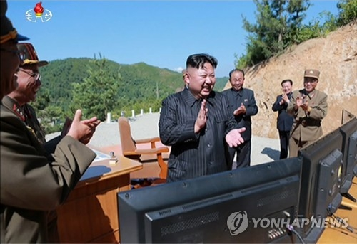 This photo taken from (North) Korean Central TV on July 4, 2017, shows North Korean leader Kim Jong-un (C) celebrating after a Hwasong-14 ICBM successfully launched from an undisclosed site. (For Use Only in the Republic of Korea. No Redistribution) (Yonhap)