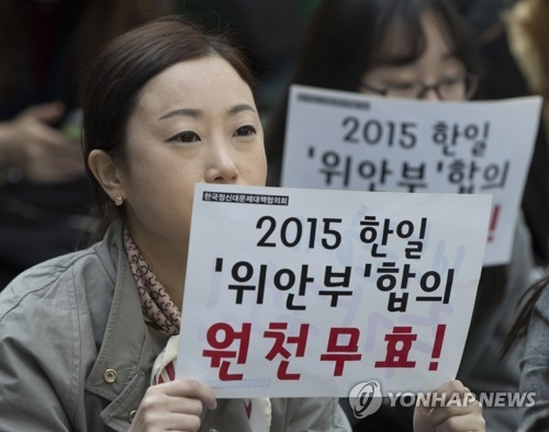 In this file photo, a protester holds a sign opposing a 2015 Seoul-Tokyo deal to settle the issue of former Korean sex slaves for Japanese troops during World War II at a rally in front of the Japanese Embassy in Seoul on March 22, 2017. (Yonhap)