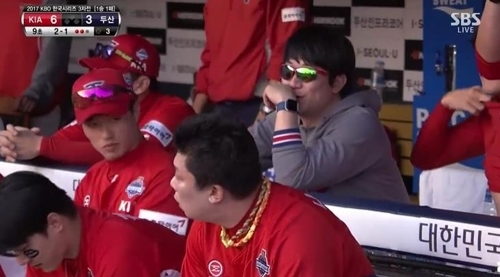 In this image captured from an SBS telecast of Game 3 of the Korean Series between the Kia Tigers and the Doosan Bears on Oct. 28, 2017, Tigers' pitcher Yang Hyeon-jong (R) can be seen wearing his Fitbit Blaze smart fitness watch in the dugout. The Korea Baseball Organization bans use of electronic communication devices in dugouts during games. (Yonhap)