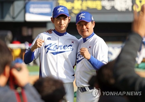 South Korean outfielder Lee Jung-hoo (L) poses with his father and national team coach Lee Jong-beom at Jamsil Stadium in Seoul on Nov. 5, 2017, during practice for the upcoming Asia Professional Baseball Championship in Tokyo. (Yonhap)