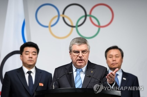In this AFP photo, International Olympic Committee (IOC) President Thomas Bach (C) delivers a statement with North Korean Sports Minister Kim Il-guk (L) and his South Korean counterpart Do Jong-hwan (R) behind him, after the IOC's North and South Korean Olympic Participation Meeting at the IOC headquarters in Lausanne, Switzerland, on Jan. 20, 2018. (Yonhap)