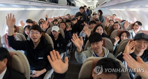 In this Joint Press Corps photo, South Korean skiers wave onboard a plane bound for North Korea on Jan. 31, 2018. (Yonhap)
