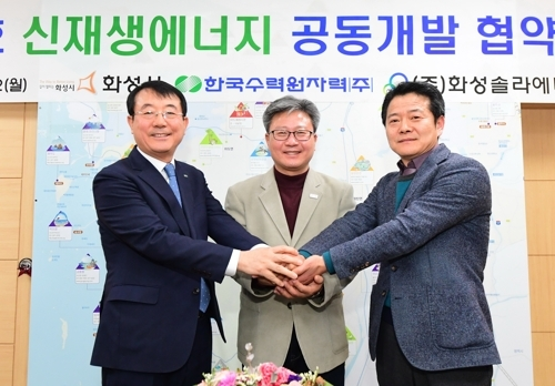 Representatives of Korea Hydro & Nuclear Power, Hwaseong Solar Energy and Hwaseong City Government pose for the camera after signing a memorandum of understanding on Feb. 12, 2018, to build a floating solar farm on Hwaseong Lake on South Korea's westesrn coast in this photo provided by KHNP. (Yonhap)