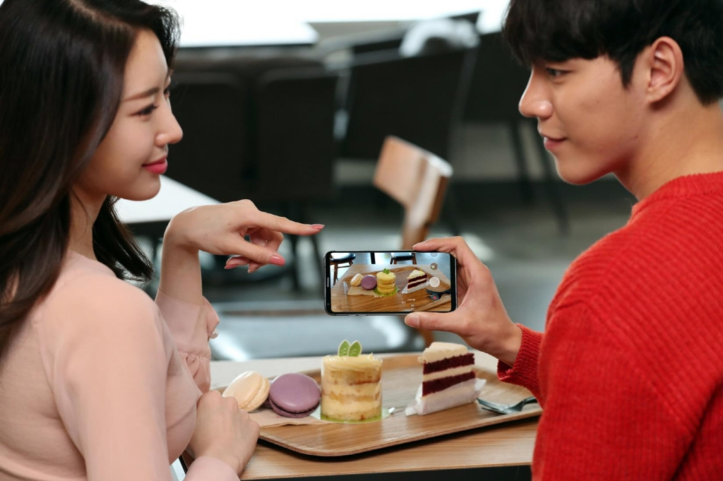 Models pose with LG Electronics Inc.'s V30S ThinQ smartphone in this photo released by the company on March 8, 2018. (Yonhap)