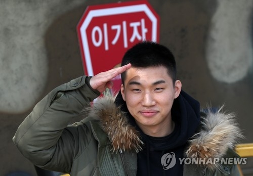 Daesung, singer of K-pop group BIGBANG, salutes fans before enlisting in the Army at the 27th Infantry Division base in Hwacheon, 118 kilometers northeast of Seoul, on March 13, 2018. (Yonhap)
