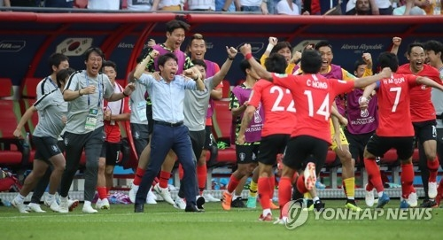 South Korean players and coaches celebrate Kim Young-gwon's goal against Germany in Group F action during the 2018 FIFA World Cup at Kazan Arena in Kazan, Russia, on June 27, 2018. South Korea won the match 2-0. (Yonhap)