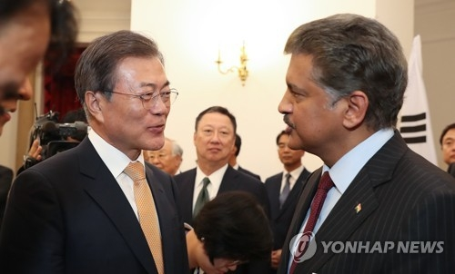 In this photo taken on July 10, 2018, South Korean President Moon Jae-in (L) talks to Anand Mahindra, chairman of Indian business conglomerate Mahindra Group, about SsangYong Motor's labor issue during a meeting between business leaders of the two countries in India. (Yonhap)
