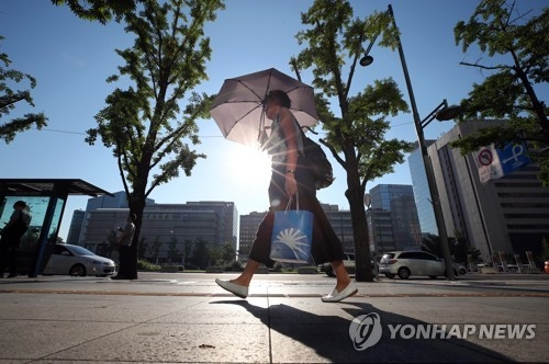 A pedestrian takes cover from the sun while walking through downtown Seoul on Aug. 1, 2018. The scorching heat wave continued on the day with no forecast of relief. (Yonhap)