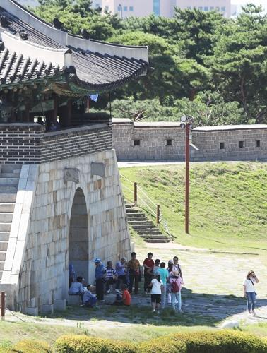 Tourists stand in a shadow created by an ancient gate in Suwon, south of Seoul, on Aug. 1, 2018, to find relief from the hot sun amid a record heat wave sweeping across South Korea. (Yonhap)