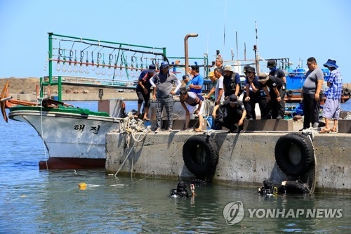 Police and Coast Guard officials search for the missing woman near a port northeast of Jeju Island on Aug. 1, 2018. (Yonhap)