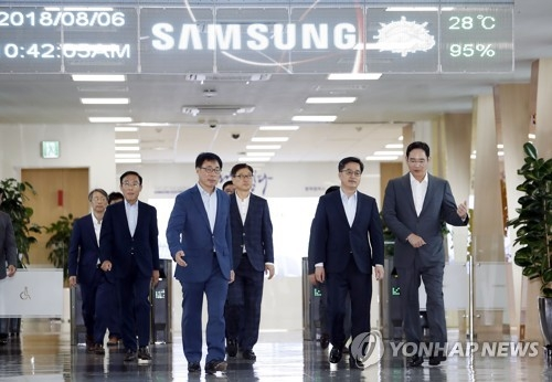Finance Minister Kim Dong-yeon (2nd from R) talks with Samsung Electronics Vice Chairman Lee Jae-yong while moving into a room for talks at the tech giant's chipmaking line in Pyeongtaek, south of Seoul, on Aug. 6, 2018. (Yonhap)