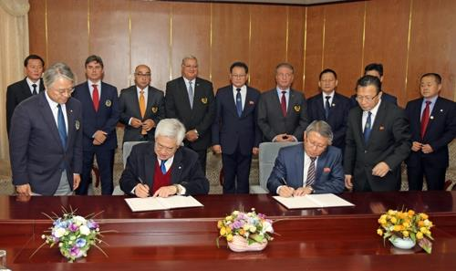 This photo provided by World Taekwondo (WT) shows WT President Choue Chung-won (2nd from L) signing an agreement with International Taekwondo Federation (ITF) President Ri Yong-son at the Yanggakdo International Hotel in Pyongyang on Nov. 2, 2018. (Yonhap)