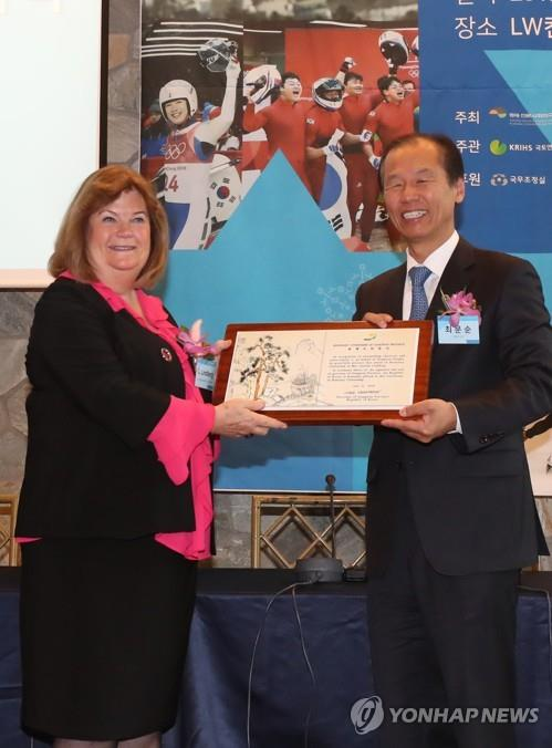 Gunilla Lindberg (L), head of the International Olympic Committee's Coordination Commission on the 2018 PyeongChang Winter Olympics, receives the certificate for honorary citizenship for Gangwon Province from Choi Moon-soon, governor of the province, during a ceremony in Seoul on Nov. 21, 2018. (Yonhap)