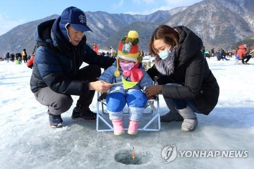 This undated file photo shows a family trying to catch smelt at the Inje Icefish Festival. (Yonhap)