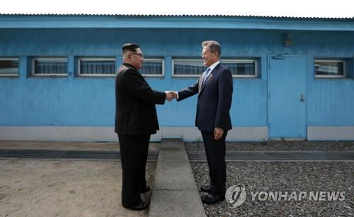 This file photo taken April 27, 2018, shows South Korean President Moon Jae-in (R) shaking hands with North Korean leader Kim Jong-un at the border village of Panmunjom ahead of their first summit. (Yonhap)