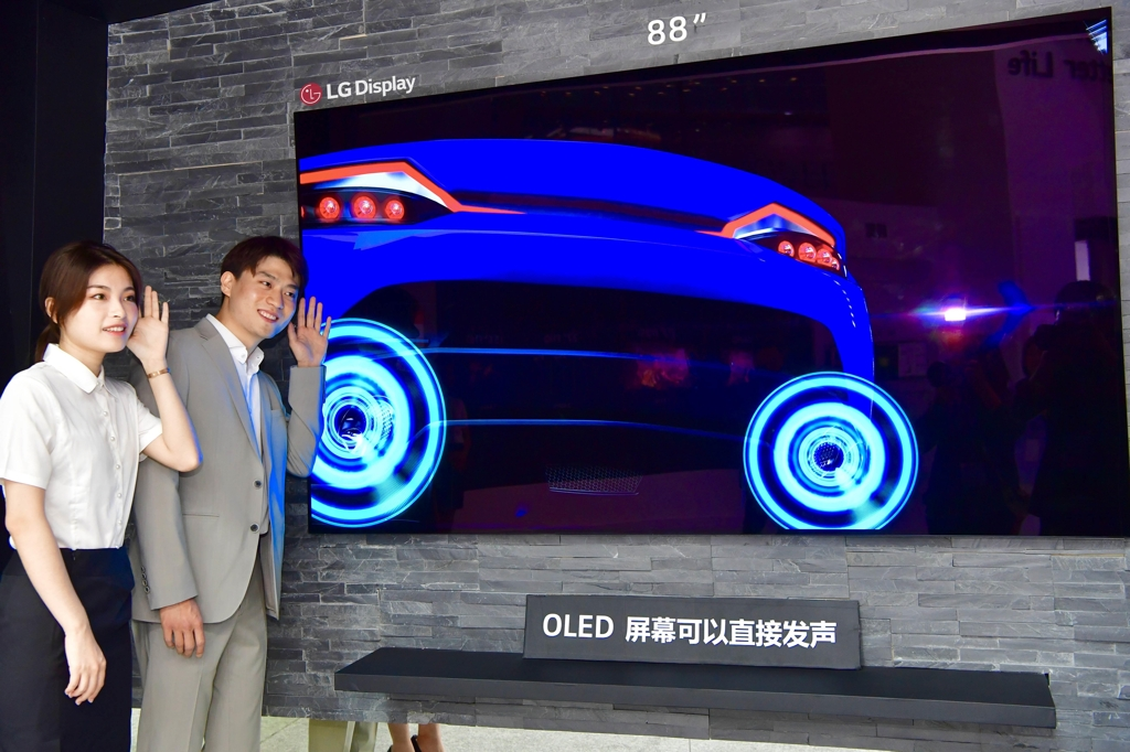 Models pose with LG Display Co.'s 88-inch OLED display at the China Information Technology Expo (CITE) 2019 in Shenzhen, China's tech hub on the southeastern coast, in this photo released by the company on April 9, 2019. (Yonhap)