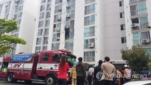 Residents of an apartment building in Jinju, South Gyeongsang Province, and firefighters watch the scene of an arson and murders on April 17, 2019. (Yonhap)