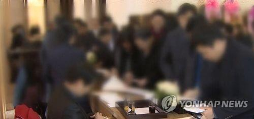 This image provided by Yonhap News TV shows wedding guests delivering cash gifts in white envelopes. (Yonhap)