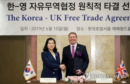 South Korean Trade Minister Yoo Myung-hee (L) and her British counterpart, Liam Fox, pose for a photo during a ceremony at a Seoul hotel on June 10, 2019, after reaching an agreement to maintain their current free trade agreement even if Britain withdraws from the European Union with no deal. (Yonhap)