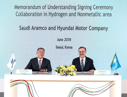 In this photo taken on June 25, 2019, and provided by Hyundai Motor, Hyundai Motor Executive Vice Chairman Chung Euisun (L) and Ahmad A. Al-Sa'adi, senior vice president of technical services at Saudi Aramco, pose for a photo after signing an MOU to cooperate on hydrogen energy in Seoul. (PHOTO NOT FOR SALE) (Yonhap)