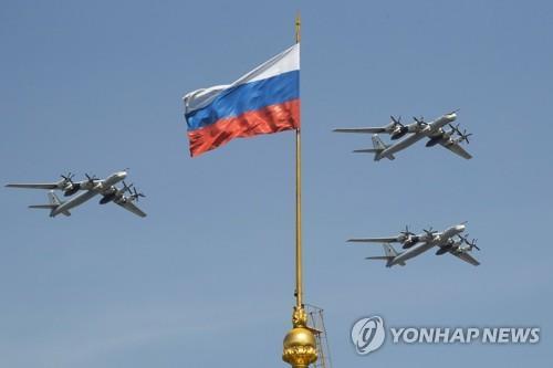 Esta foto do arquivo do AP, tomada o 4 de maio de 2018, mostra bombardeiros estratégicos do russo Tu-95 que voam após uma bandeira do russo no complexo de Kremlin durante um ensaio para a parada militar de Victory Day em Moscou, Rússia.  (Yonhap)