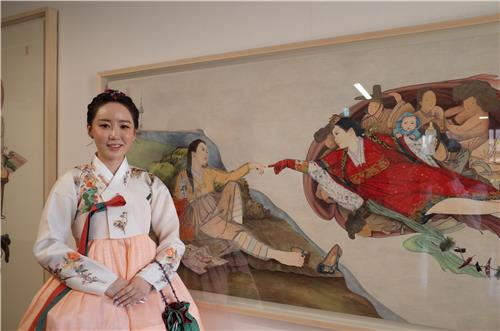 "This photo shows artist Kim Hyun-jung with her work ""Marriage: Difference Between Heaven and Earth,"" which is being exhibited at an art space of Seoul National University's visual art school, on Sept. 18, 2019. (Yonhap)"