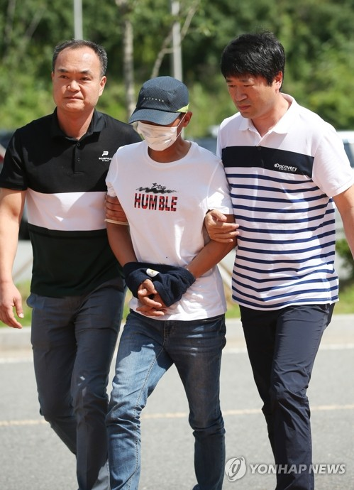 In this file photo dated July 8, 2019, an alleged wife batterer (C) arrives at a court in the southwestern port city of Mokpo to attend a hearing on the legality of his arrest. The 36-year-old, whose identity was withheld, allegedly beat his Vietnamese-born wife for three hours at their home in Yeongam, about 310 kilometers south of Seoul, on July 4 for not speaking Korean well and talking back. (Yonhap)