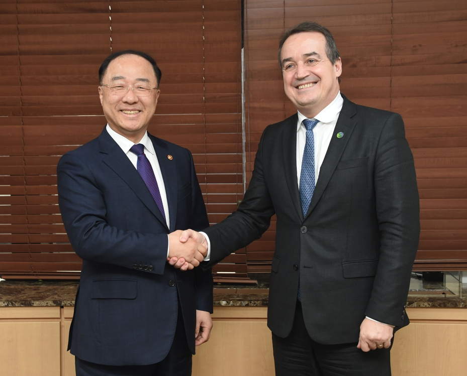South Korean Finance Minister Hong Nam-ki (L) shakes hands with Yannick Glemarec, executive director of the U.N. Green Climate Fund, at the government complex building in central Seoul on Oct. 10, 2019, in this photo provided by the ministry. (PHOTO NOT FOR SALE) (Yonhap)