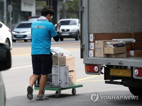 This file photo taken on Aug. 8, 2018, shows a deliveryman from Coupang Inc. transporting packages in Seoul. (Yonhap)