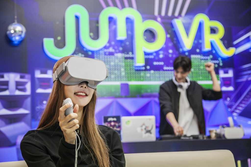 Models enjoy SK Telecom Co.'s Virtual Social World, a virtual reality (VR) playground, with the VR headset Oculus Go, in this photo provided by the mobile carrier on Nov. 19, 2019. (PHOTO NOT FOR SALE) (Yonhap)