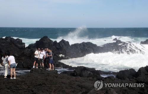 This file photo shows tourists taking photos on a beach of Jeju Island. (Yonhap)