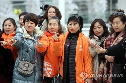 This file photo taken on Jan. 8, 2020, shows employees of China's Yiyongtang posing in front of a shopping mall in Incheon during their incentive trip to South Korea. (Yonhap)