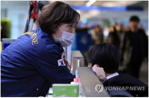 A South Korean quarantine official (L) checks the temperature of a person who just arrived at Incheon International Airport, west of Seoul, on Jan. 23, 2020. The National Quarantine Station is operating health checkpoints at all major airports to screen people for fever and other symptoms of the Wuhan coronavirus. (Yonhap)