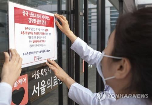 Hospital staff in Seoul put up a notice informing people of risks associated with the Wuhan coronavirus on Jan. 24, 2020. (Yonhap)