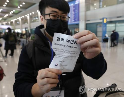 A Chinese visitor shows off his quarantine certificate after entering South Korea via Incheon International Airport, west of Seoul, on Feb. 4, 2020. (Yonhap)