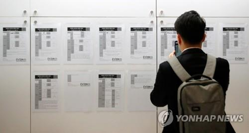 This file photo shows an unidentified job seeker taking a picture of job openings at an exhibition in southern Seoul. (Yonhap)