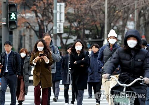 People wearing masks cross a road on their morning commute in Seoul amid the spread of a new coronavirus in this file photo taken Jan. 29, 2020. (Yonhap)