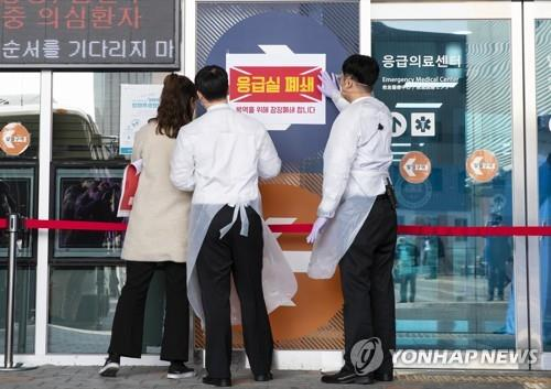 Workers at Hanyang University Hospital in Seoul post a notice saying the emergency center is temporarily closed on Feb. 19, 2020, to prevent the spread of the novel coronavirus. (Yonhap)