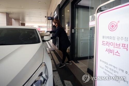 "A Lotte Department Store employee hands over products to a customer of the retailer's ""drive-up and pick-up"" service in Gwangju, southwestern South Korea, on March 19, 2020. (Yonhap)"