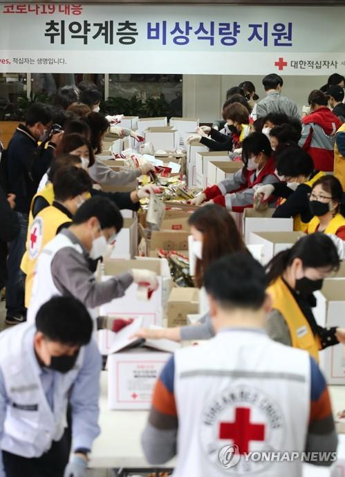 Volunteers prepare emergency relief kits packed with basic necessities like instant food at an office of the National Red Cross in Seoul on March 27, 2020, for delivery to impoverished people experiencing difficulties amid the spread of the new coronavirus. (Yonhap)