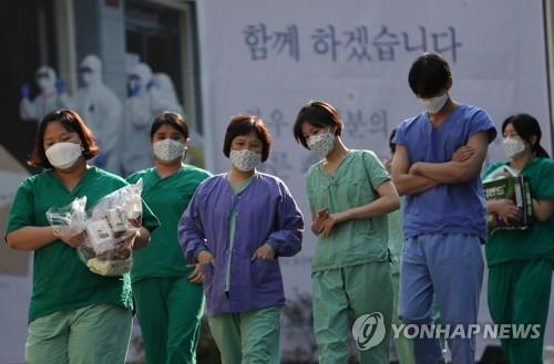 Medical workers walk to a resting place after working a shift for coronavirus patients at Dongsan Hospital in Daegu, 302 kilometers southeast of Seoul, on April 9, 2020. (Yonhap)