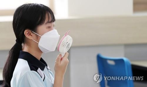 A student cools herself with a hand-held fan inside a classroom in Chuncheon, Gangwon Province, on June 8, 2020. (Yonhap)