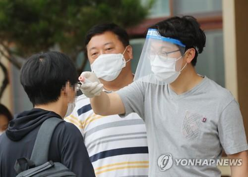 A exam taker undergoes a body temperature check at a school in the southern city of Gwangju where a national examination for recruitment of entry-level civil servants was held on July 11, 2020. (Yonhap)