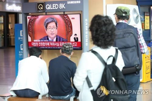 People watch the live broadcast of the Supreme Court's ruling for Gyeonggi Province Gov. Lee Jae-myung in Seoul Station in the capital city on July 16, 2020. (Yonhap)