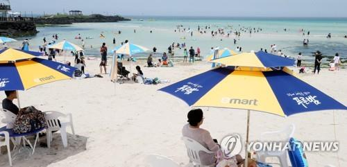 Tourists and Jeju Island residents enjoy themselves at a beach on the southern resort island on July 31, 2020, amid sweltering heat. (Yonhap)